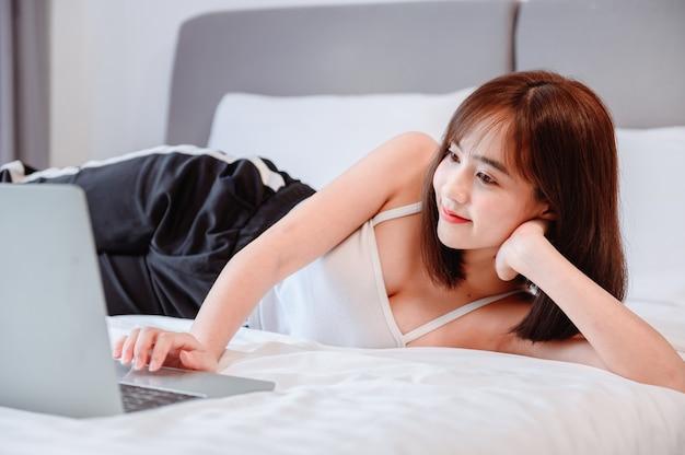 アジアの女性はオンラインで働き、自宅の寝室でリラックスします。社会的距離と新しい通常のライフスタイル。