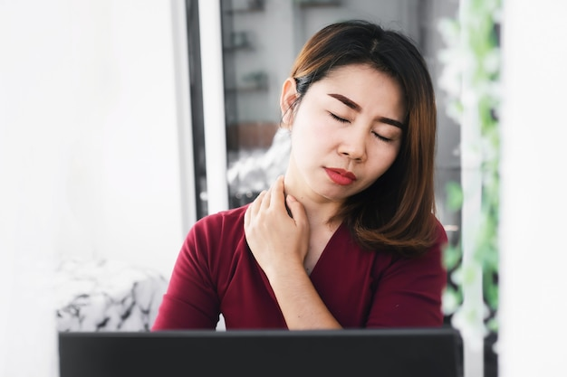 Asian woman worker having neck pain and sore muscles  office syndrome concept