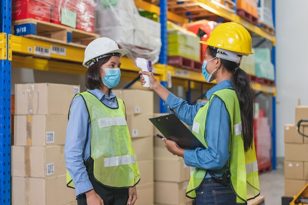 Asian woman worker wear face mask in safety vest using thermometer infrared scan to check body temperature with colleague before working in warehouse factory during coronavirus pandemic