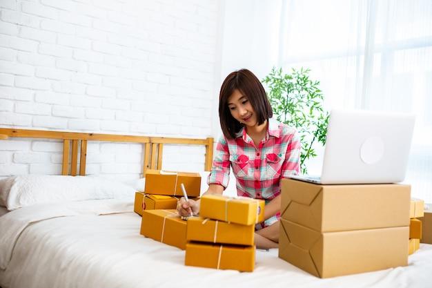 Азиатская женщина работает дома для доставки клиенту