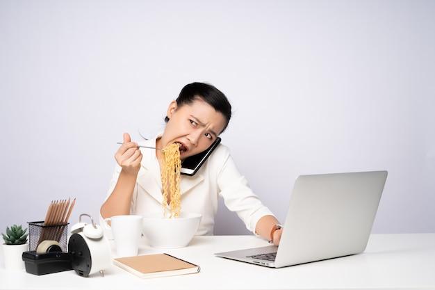 사무실에서 라면을 먹고 열심히 초과 근무를 하는 아시아 여성. 화가 사업가 바쁘고 배고픈 과로.