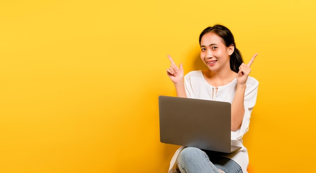 Asian woman working on his laptop computer and a happy smile happy work concept on a yellow background in the studio