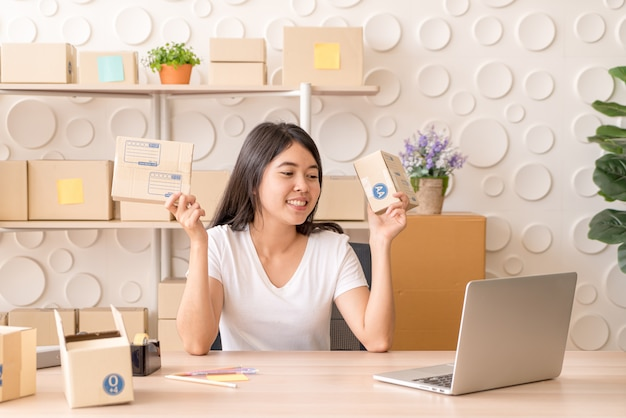 Asian woman working at home with packing boxes