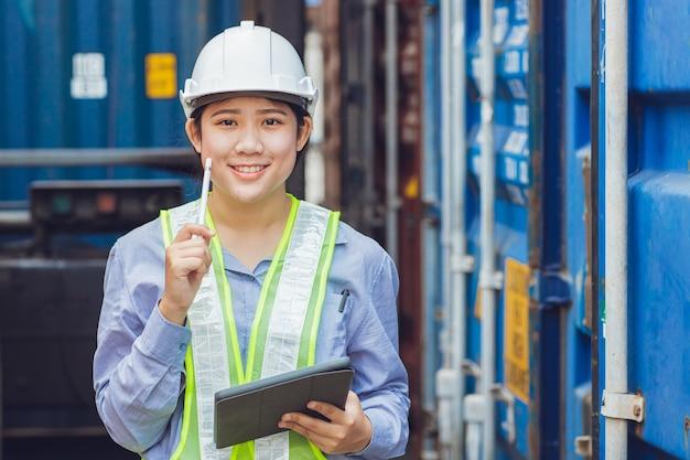 Азиатская женщина, работающая в зоне погрузки и логистики грузов, проверяет таможню импортно-экспортного контейнера портрет улыбается