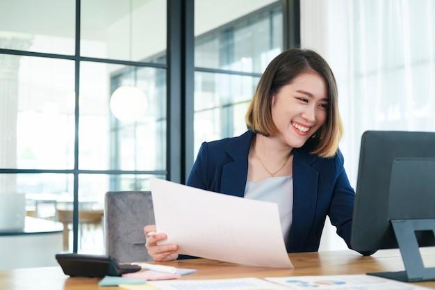 아시아 여자 작업 노트북입니다. 사무실에서 노트북 컴퓨터 작업에 바쁜 비즈니스 우먼.