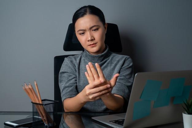 노트북에서 일하는 아시아 여성은 사무실에 앉아 신체 통증으로 아팠습니다.