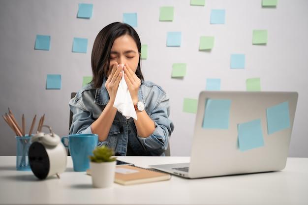 Азиатская женщина, работающая на ноутбуке, заболела лихорадкой, сидя в домашнем офисе. . работа из дома. концепция профилактики коронавируса covid-19.