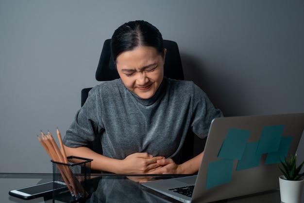 노트북에서 일하는 아시아 여성은 사무실에 앉아 복통으로 아팠습니다.