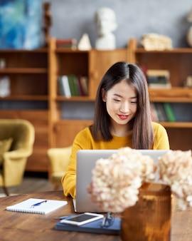 自宅やカフェでラップトップに取り組んでいるアジアの女性。若い女性