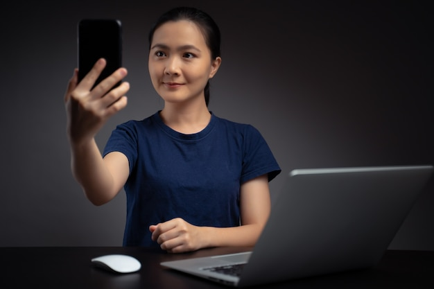 노트북에서 일하는 아시아 여성은 얼굴 인식 시스템을 사용하여 스마트 폰으로 얼굴을 스캔합니다.