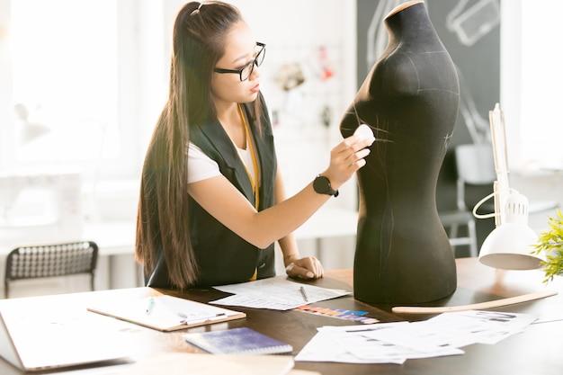 Asian woman working in sunlit atelier