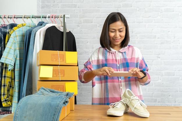 オンラインで販売するポストのスマートフォンで靴に写真を撮って働くアジアの女性