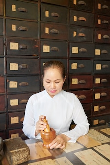 Asian woman working at tradional pharmacy