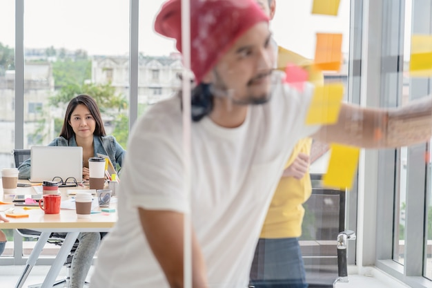 Asian woman working which have photo blurred of creative writing and pointing the post it
