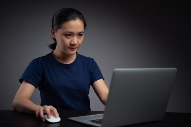 노트북을 사용하는 아시아 여자. 사무실에서 노트북에서 일하는 비즈니스 여자.