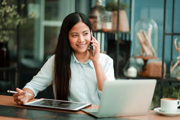 Asian woman working with laptop computer in coffee shop cafe