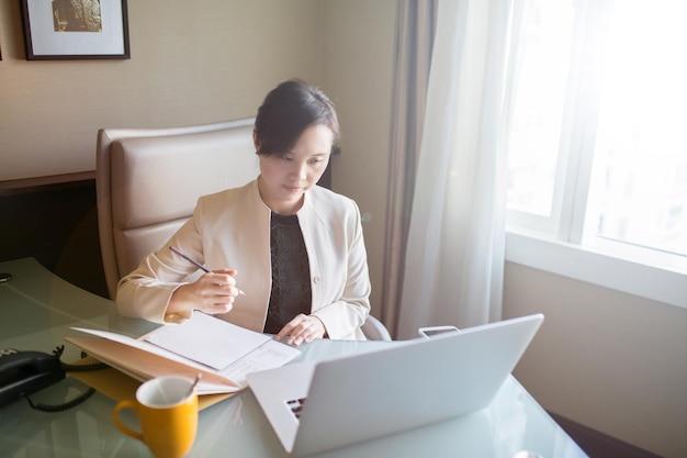 Азиатская женщина, работающая с ноутбуком в офисе