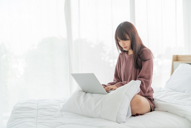 Азиатская женщина, работающая с ноутбуком на кровати у себя дома