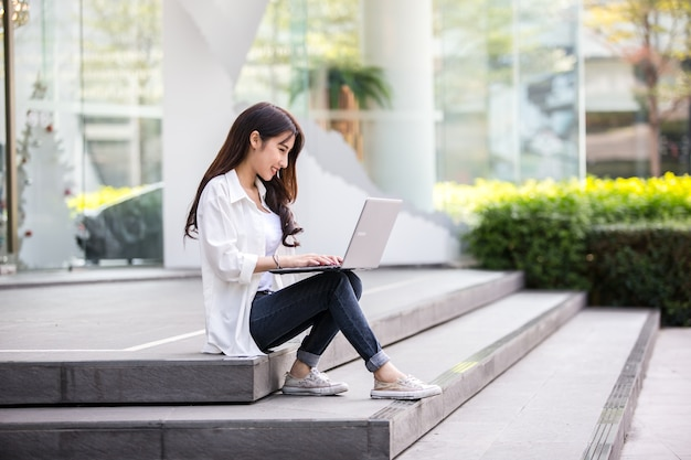Asian woman working with laptop while sitting on the steps outside the office