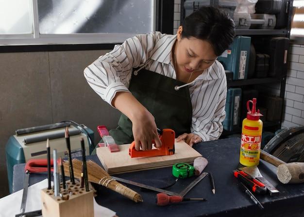 Donna asiatica che lavora con il legno