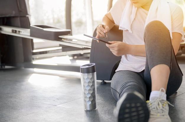 アジアの女性のトレーニングとgymで一人でオンラインで働いています。社会的距離と新しい通常のライフスタイル。
