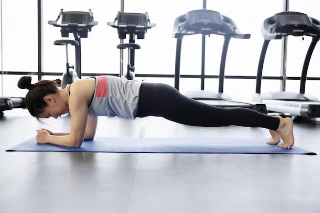 Азиатская женщина в позе планки на коврике для йоги