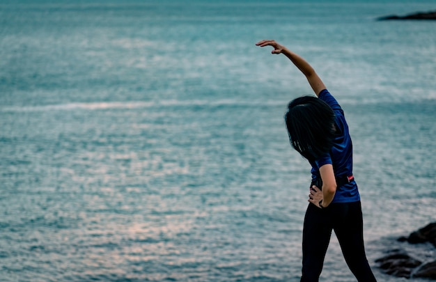 美しい日の出の空と石のビーチで午前中にアジアの女性のトレーニング。実行する前に体を伸ばして女性ランナーに合います。健康的なライフスタイルのための有酸素運動。一人で女の子のトレーニング。