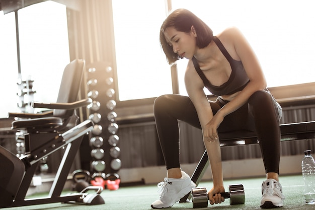 Asian woman workout with dumbbells in gym.