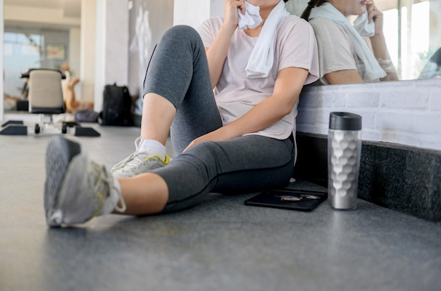 Asian woman workout and working online alone at gym. social distancing and new normal lifestyle.