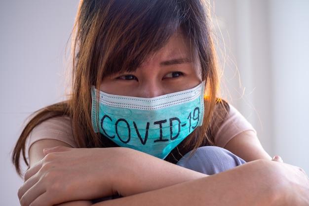 Asian woman worry and fears wearing mask、writes covid-19武漢での2019-ncovウイルス感染の状況世界の致命的な疫病コロナウイルスを保護するためのマスクされた概念