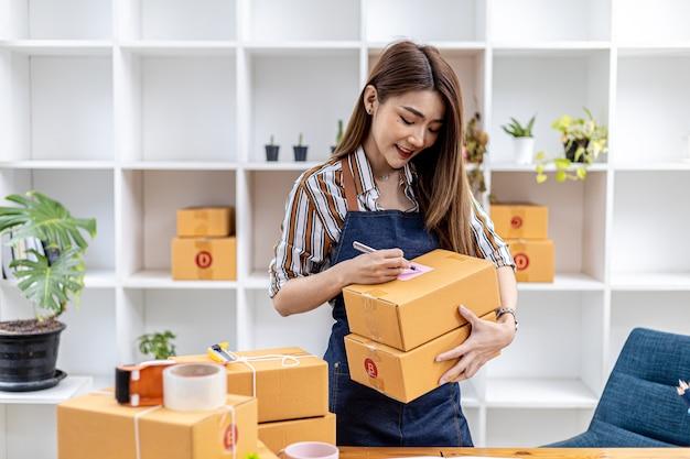 아시아 여성이 소포 상자에 고객의 배송 정보를 쓰고 온라인 상점을 소유하고 개인 택배 회사를 통해 고객에게 제품을 배송합니다. 온라인 판매 개념입니다.