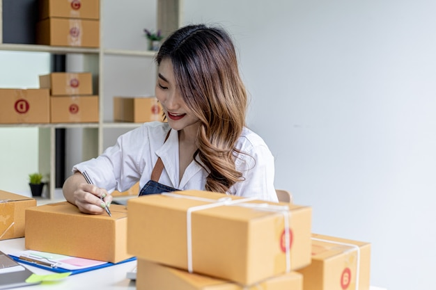 Asian woman writing customer's shipping information on parcel box, she owns an online store, she ships products to customers through a private courier company. online selling concept.
