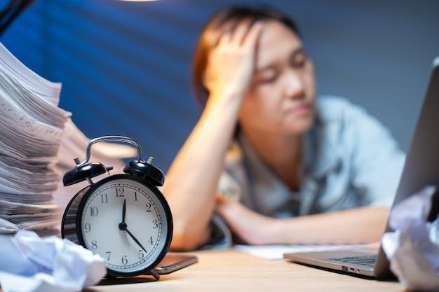 Азиатская женщина, написание документов в сверхурочное время в ночное время. крайний срок работы в офисе. офицер девушка головная боль и занята своей работой. несчастная и стресс.