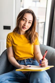 白いモダンな椅子に置かれたメモ帳で書くアジアの女性