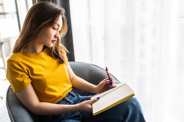 Asian woman writing in notepad placed on white modern chair
