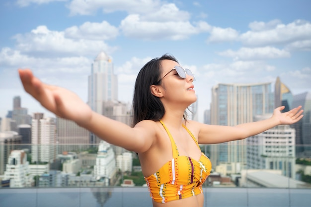 Asian woman in yellow swimsuit relax in rooftop swimming pool with bangkok city