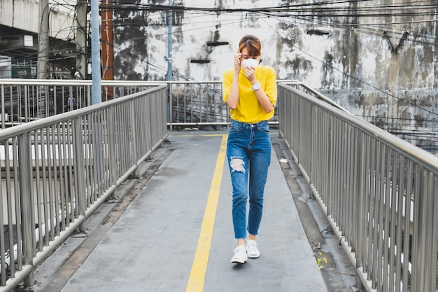 Asian woman yellow t-shirt wearing the n95 respiratory protection mask against air pollution walking in bangkok