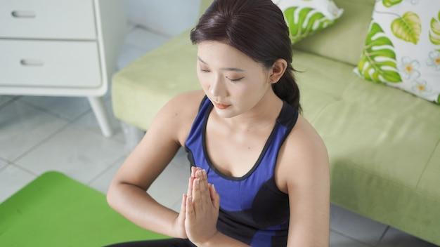 焦点を当てて手のエクササイズをしている自宅でアジアの女性のヨガ