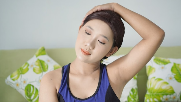 Asian woman yoga at home warming up head to side