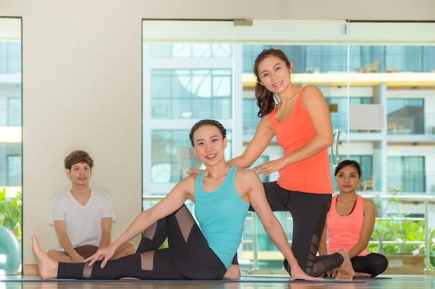 スタジオの教室でアジアの女性のヨガマスター教授の学生