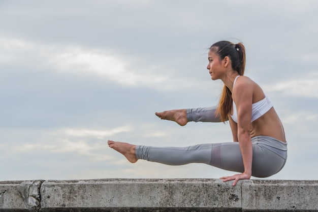 Asian woman in yoga pose on top of wall.