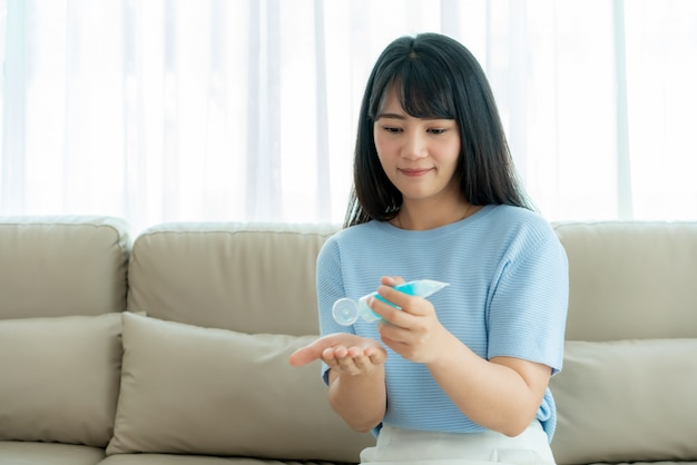 Asian womanl using alcohol antiseptic gel, prevention, cleaning hands frequently, prevent infection, outbreak of covid-19 wash hands with hand sanitizer to avoid contaminating.