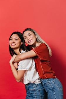 Азиатские женщины в белых и красных футболках позируют на изолированной стене