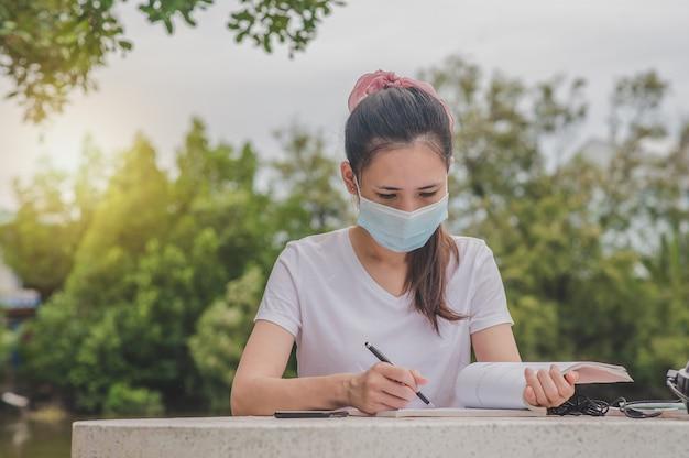 アジアの女性が大学で屋外に座って本を読んで身に着けているフェイスマスク