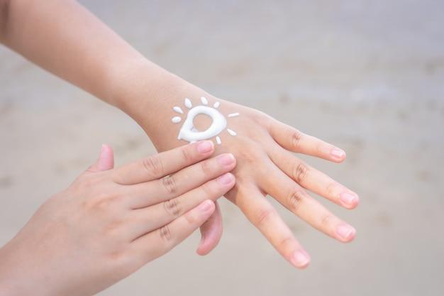 아시아 여성은 손과 팔에 자외선 차단제를 바르십시오. 햇빛으로부터 피부를 보호하기 위해