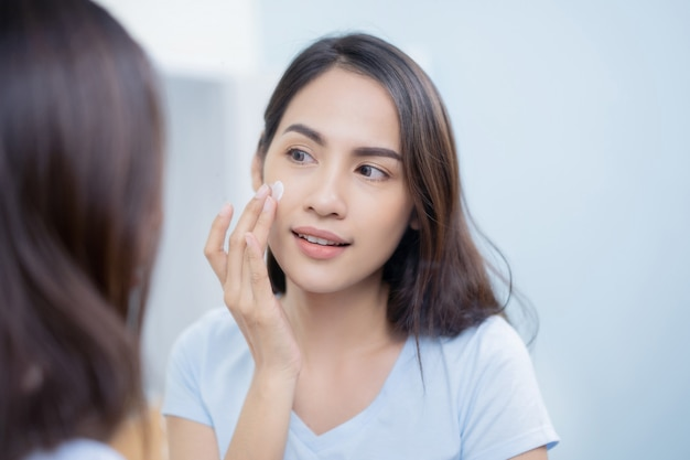 Asian women applying face lotion