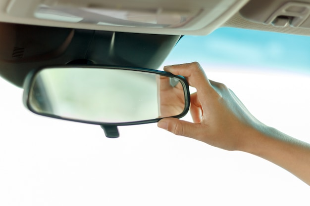 Asian women are adjusting the rearview mirror of the car