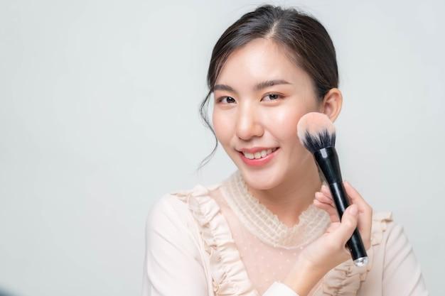 アジアの女性が楽屋の化粧台でファンデーションを塗っています。