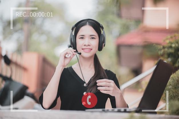 アジアの女性はコールセンターとスクリーンビデオの通話記録です