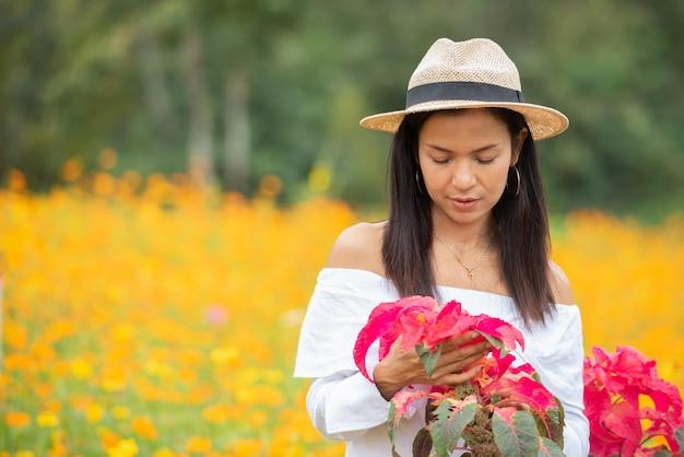 아시아 여성은 공원에서 붉은 꽃을 즐기고 있습니다.